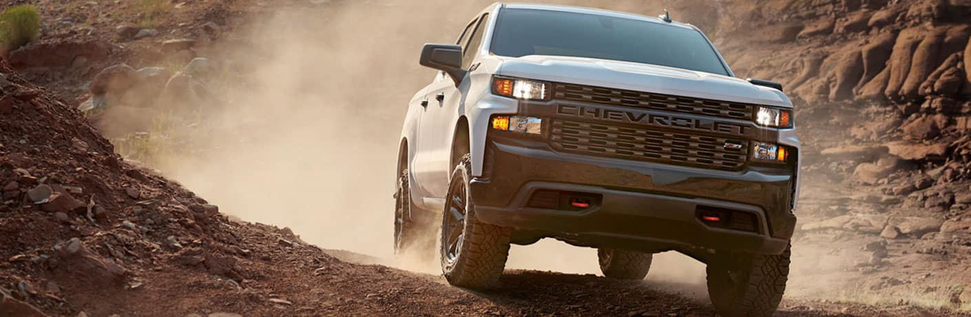 White 2020 Chevy Silverado 1500 powers triumphantly through a cloud of dirt and dust.