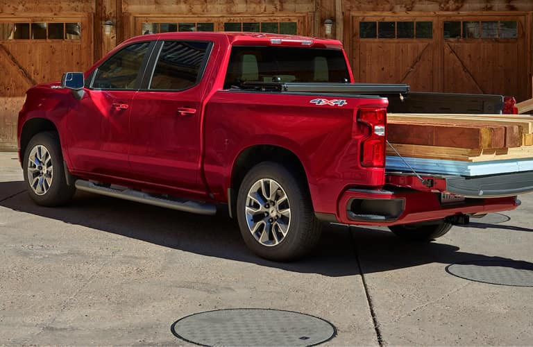 Red 2020 Chevy Silverado 1500 with wooden planks in the bed.