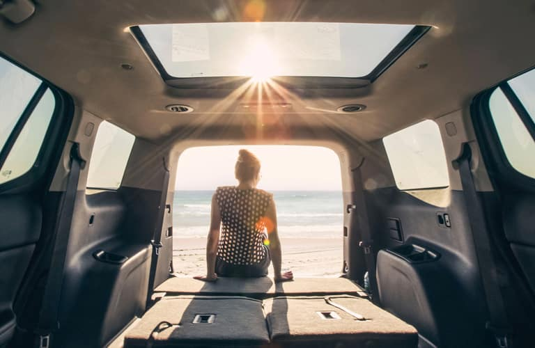 A woman sits on the tail end of a 2020 GMC Acadia Denali and gazes as the sun sets over the ocean beyond.