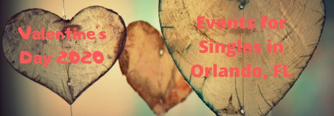 "A couple of wooden hearts hang with red writing inscribed on them, informing ""Valentine's Day 2020"" ""Events for Singles in Orlando, FL"""