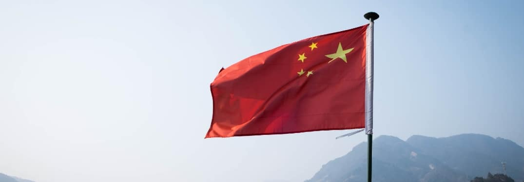 A Chinese flag blows against a clear sky.