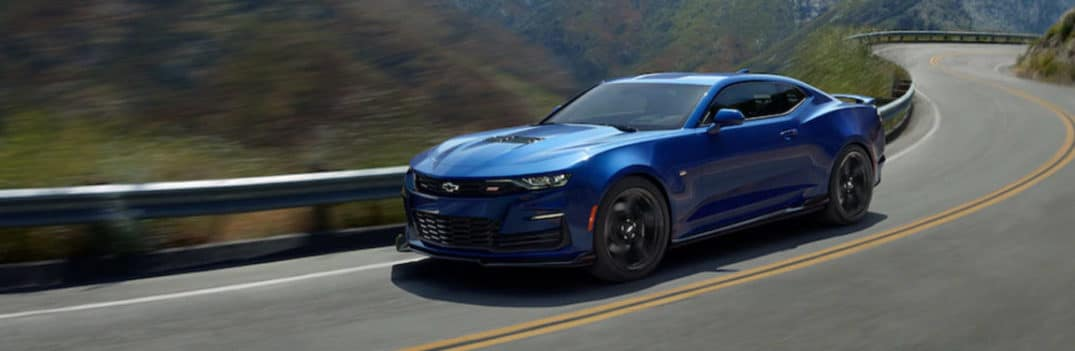 Blue 2020 Chevy Camaro cruises around a highway bend.