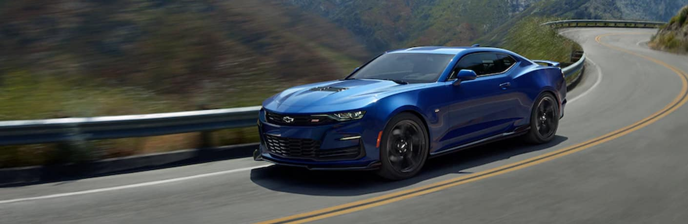 A blue 2020 Chevy Camaro zips around a highway bend.