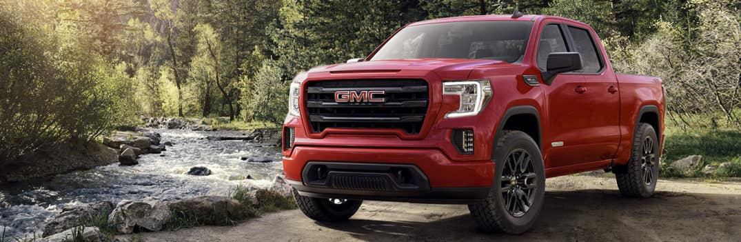 Red 2020 GMC Sierra 1500 parked by a small stream in a forest.