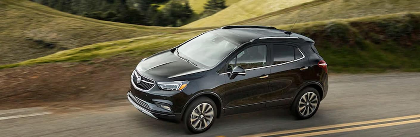 A 2020 Buick Encore rolls through a lush hilly countryside.