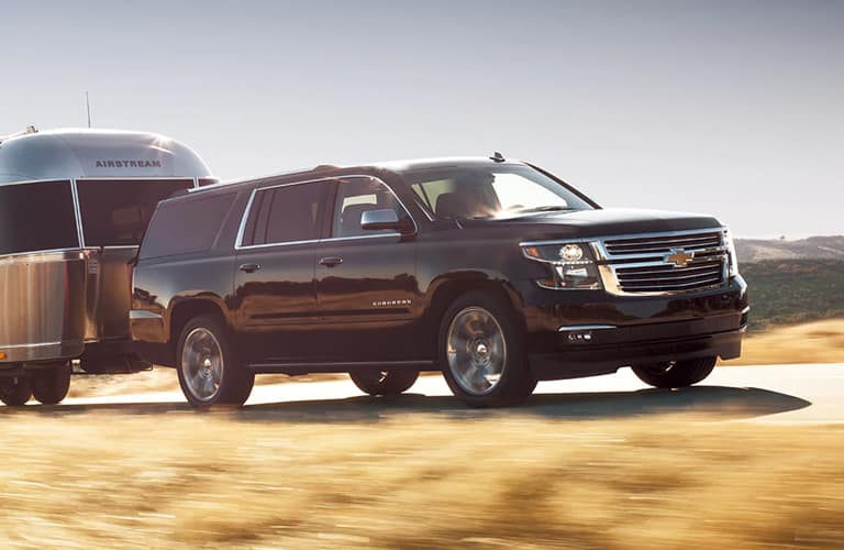 2020 Chevy Suburban pulls a camper through the countryside