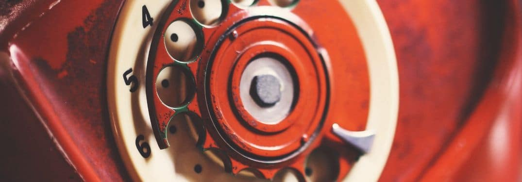 Close-up image of an old red rotary phone dial