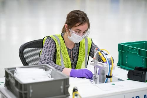 A woman in a GM plant sews masks to combat the coronavirus