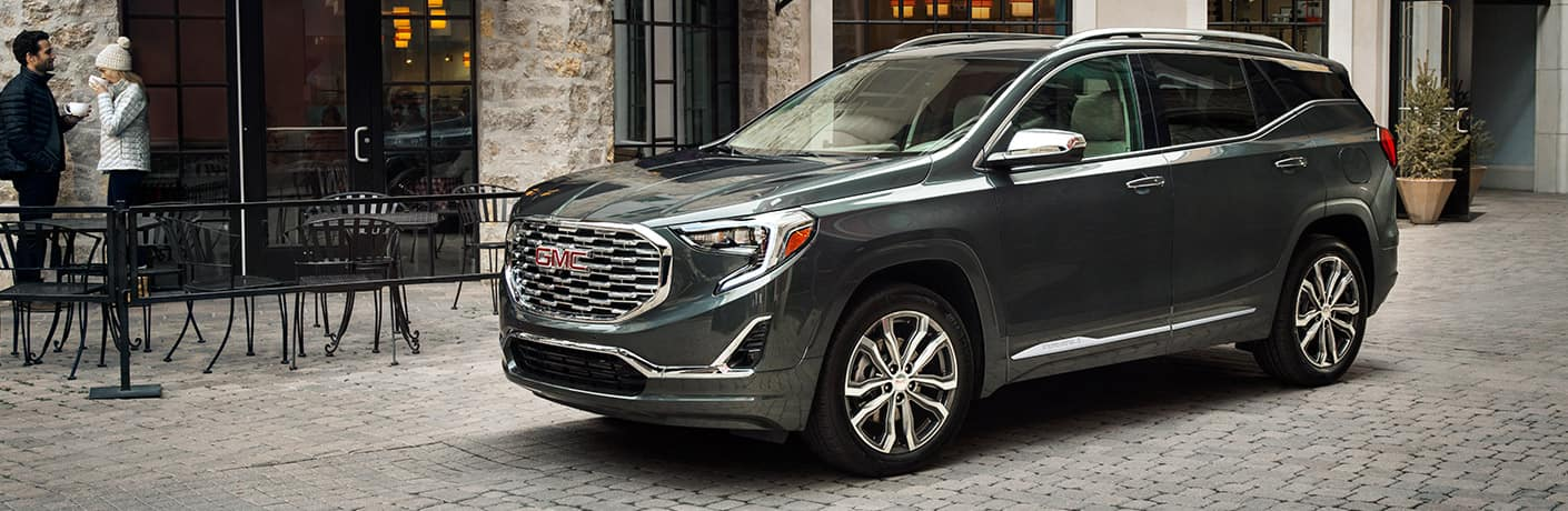 2019 GMC Terrain Denali parked on a cobblestone street in front of a coffee shop.