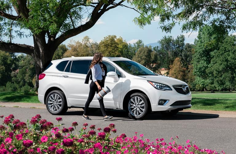 Woman walks alongside a white 2020 Buick Envision Essence parked under the bent branches of a tree.