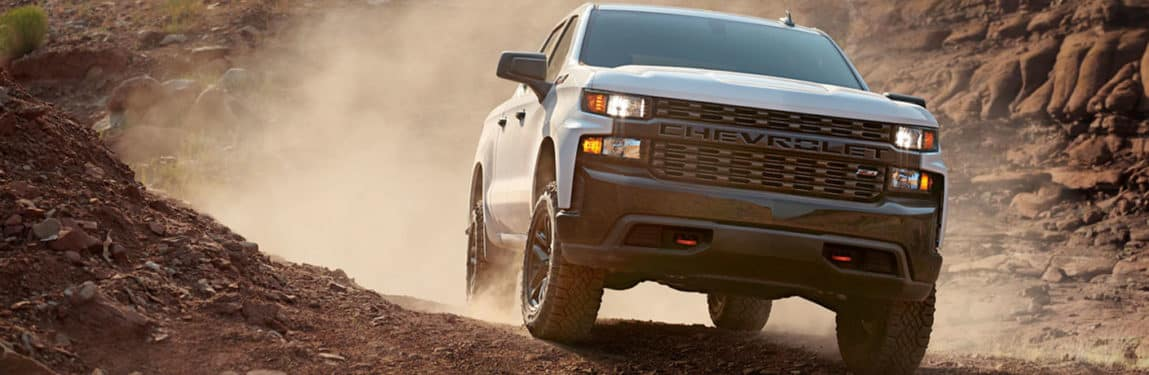 Beefy 2020 Chevy Silverado 1500 drives off road spewing a cloud of dusty.
