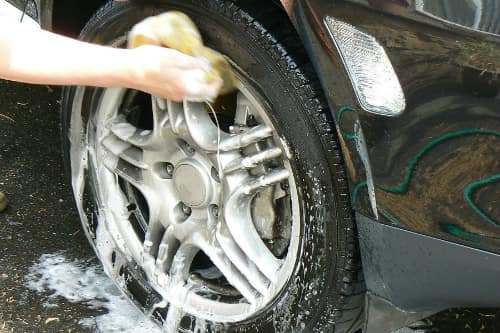 A wheel is scrubbed with a soapy sponge