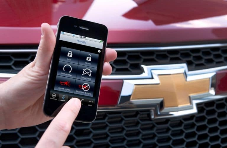 Finger dangles over remote start button on an iPhone 4 RemoteLink app by a large Chevy logo