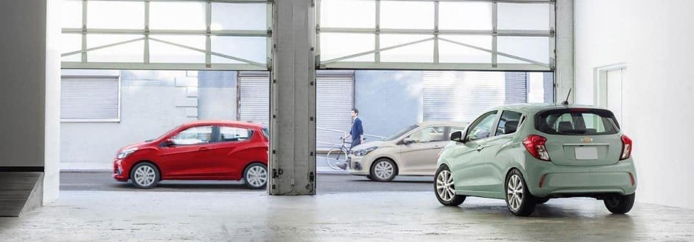 Several 2017 Chevy Spark models surrounding a weird garage