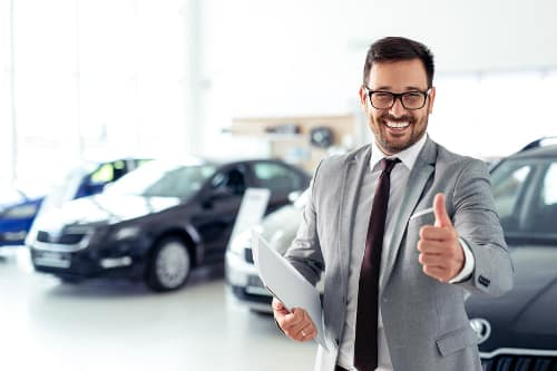 """Salesman in a dealership happily gives the """"thumbs up"""""""