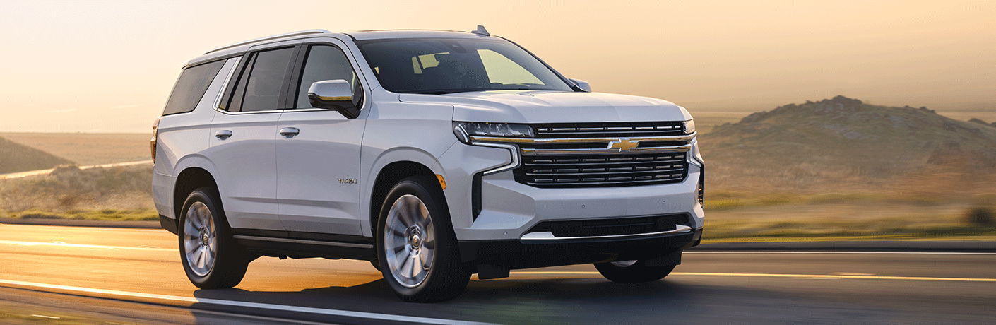 White 2021 Chevy Tahoe drives through a sun drenched morning mist