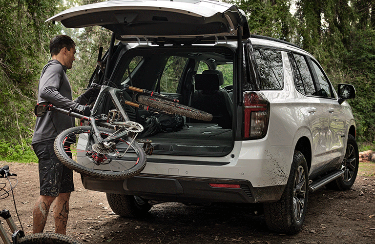 Man loads a bicycle into the back of a white 2021 Chevy Tahoe