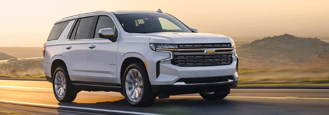 White 2020 Chevy Tahoe drives through a sun-drenched fog