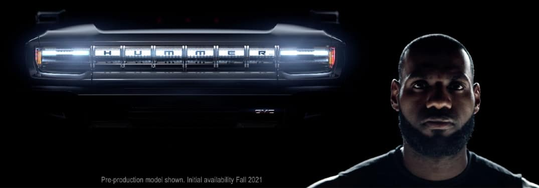 Lebron James' face looms beside the glowing grill of a pre-production 2022 GMC Hummer EV