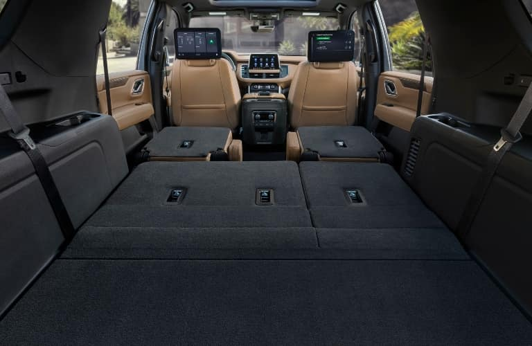 Rear cargo area with all seats folded down in a 2021 Chevy Suburban