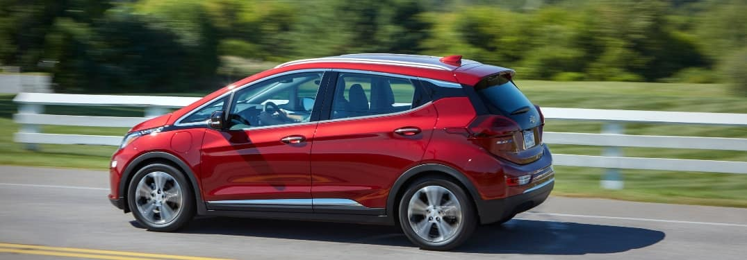 Red Chevy Bolt EV on a highway