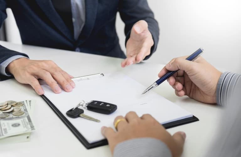 Man signs form with some car keys sitting on it