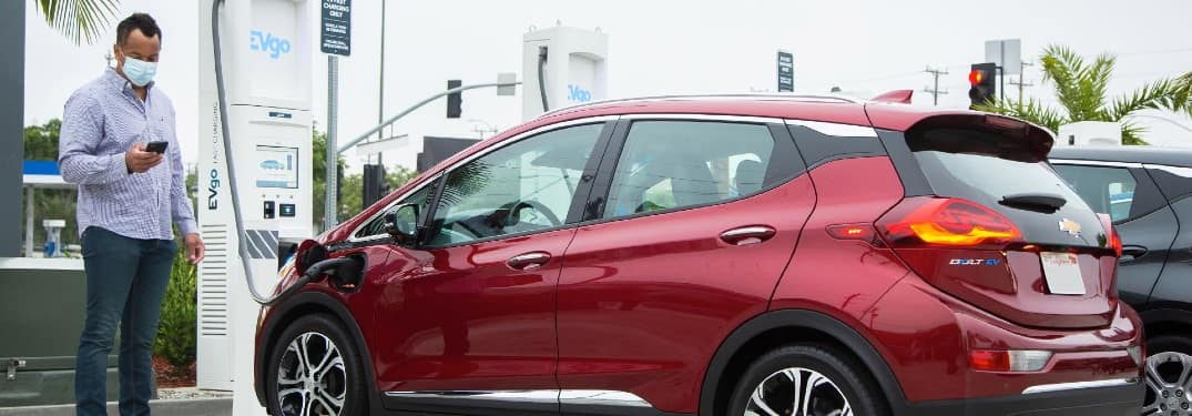 Man with facemask charges his red Chevy Bolt