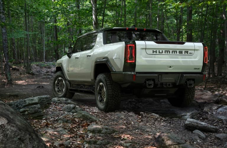 Rear view of a 2022 GMC HUMMER EV SUT in a forest