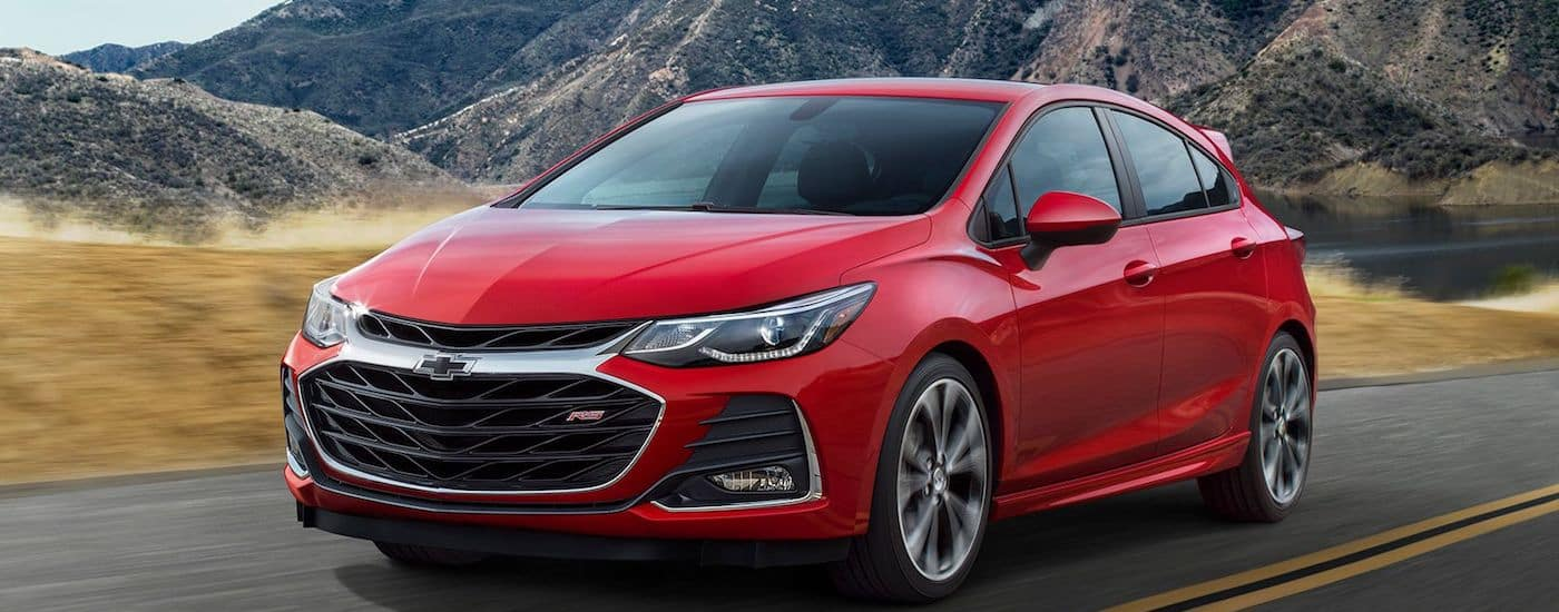 A red 2019 Chevy Cruze in front of green mountains
