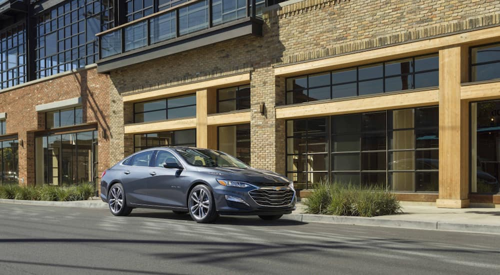 A grey 2019 Chevy Malibu in front of a large brick and wood building