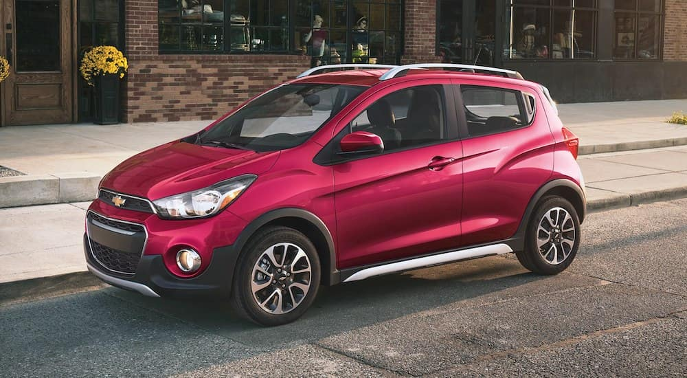Red 2019 Chevy Spark on street in front of brick building