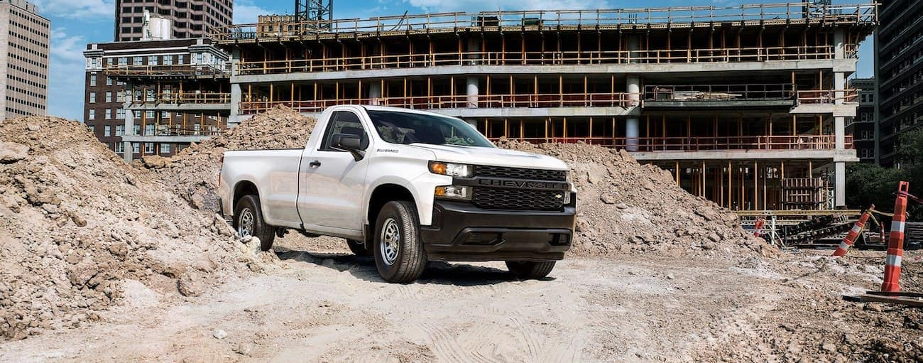 White 2019 GMC Sierra 1500 driving between dirt piles at construction site