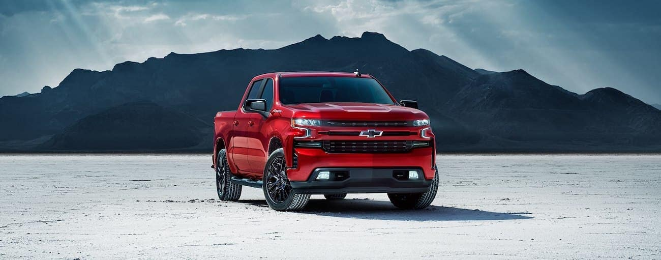 Red 2019 Chevy Silverado in salt flat with mountain in back