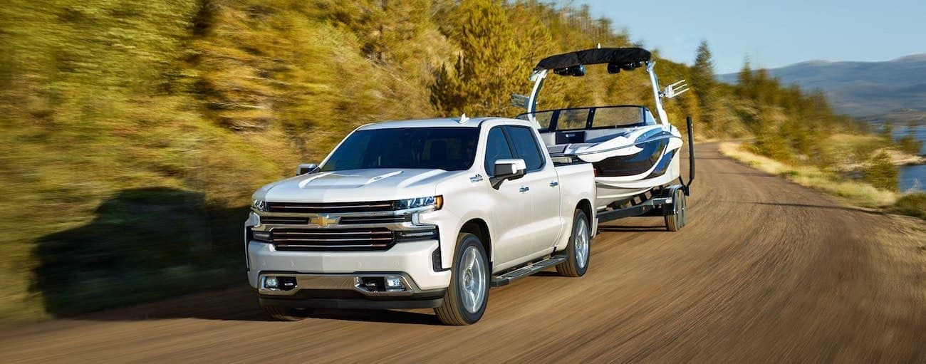 White 2019 Chevy Silverado towing boat on winding mountain road, lake to side