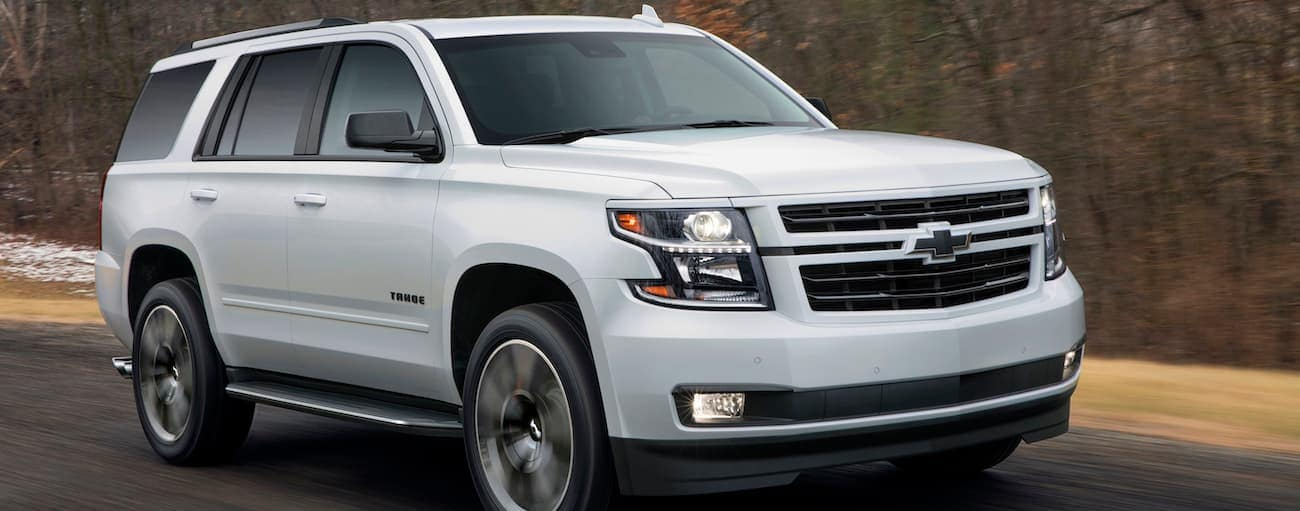 A white 2019 Chevy Tahoe RST driving on a wooded road