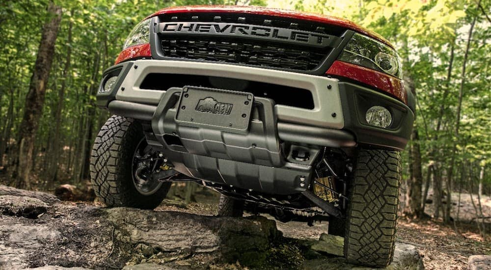 New Chevy Trucks including this red 2019 Chevy Colorado ZR2 Bison climbing over rocks