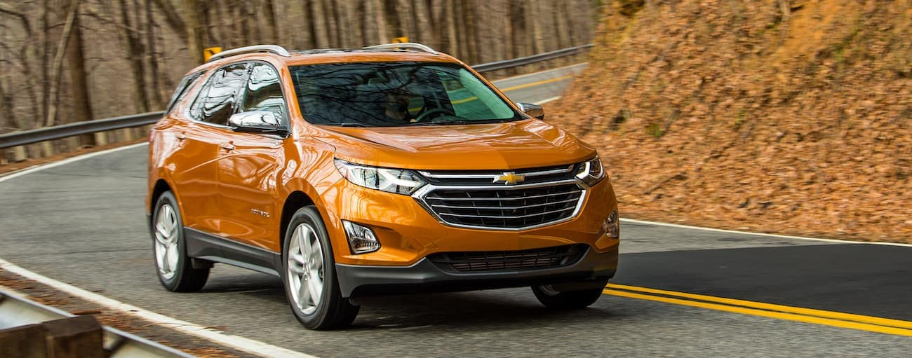 An orange 2019 Chevrolet Equinox driving on a leave-covered road