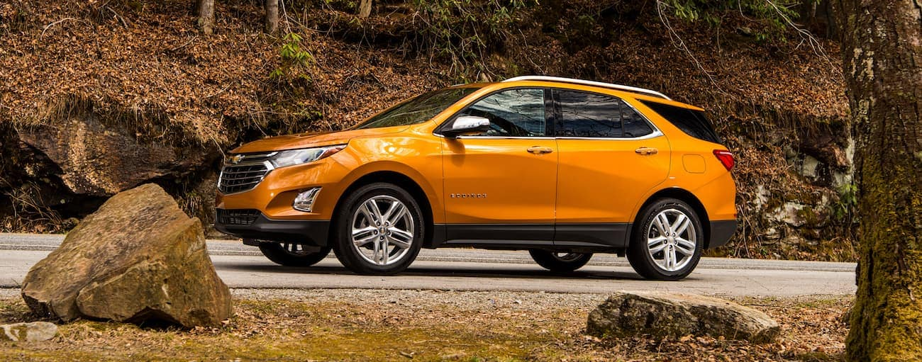 An orange 2019 Chevy Equinox drives up a leave-covered hill