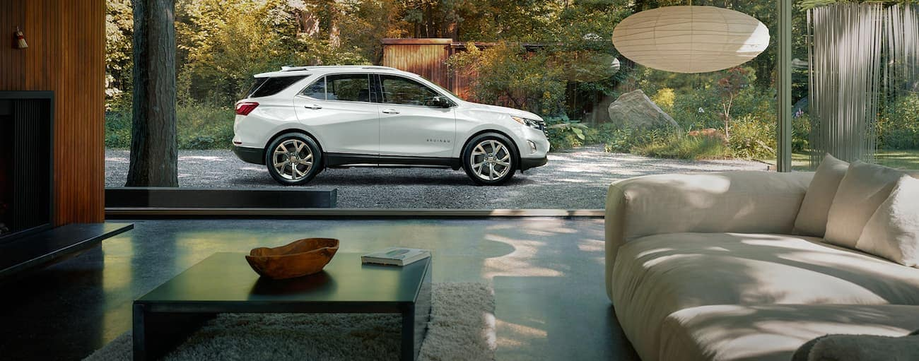 A white 2019 Chevrolet Equinox viewed through a window from a modern living room