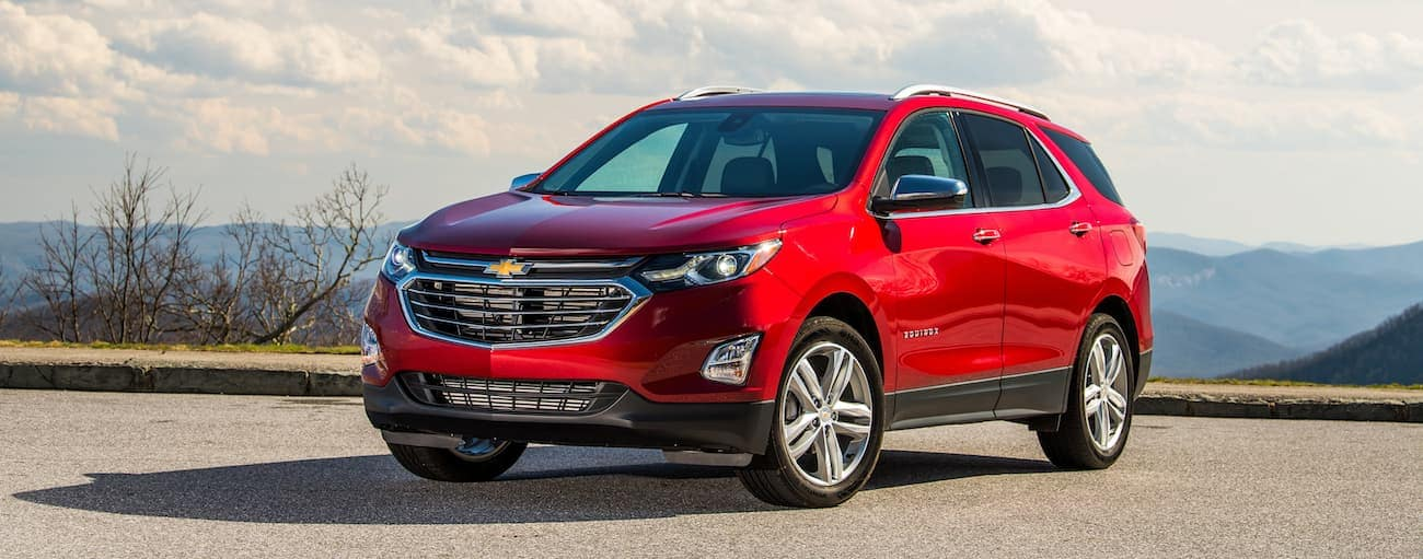 A red 2019 Chevy Equinox atop a hill with mountains a ways off in the background