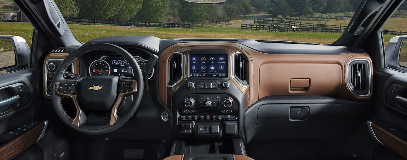 A brown and black leather interior of a 2019 Chevy Silverado overlooking a field with horses