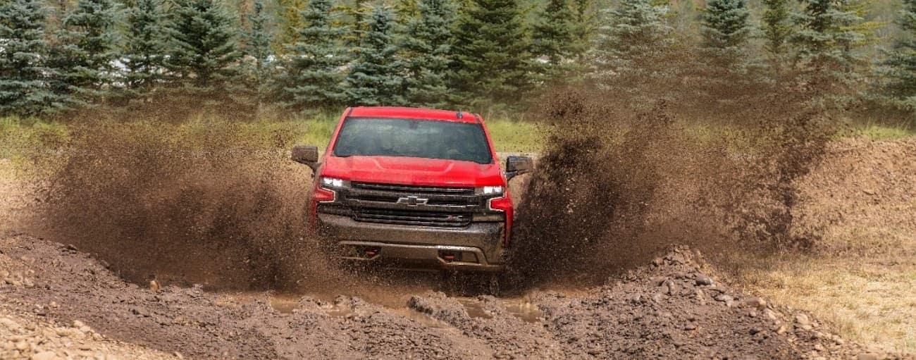 A red 2019 Chevy Silverado TrailBoss splashing through mud