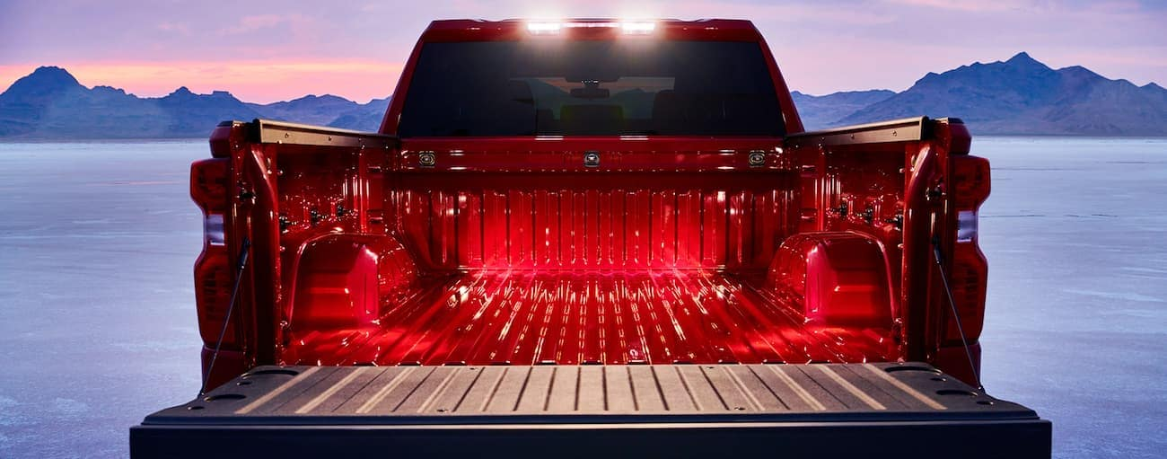 A red 2019 Chevy Silverado in the desert with mountains in the back and the tailgate open