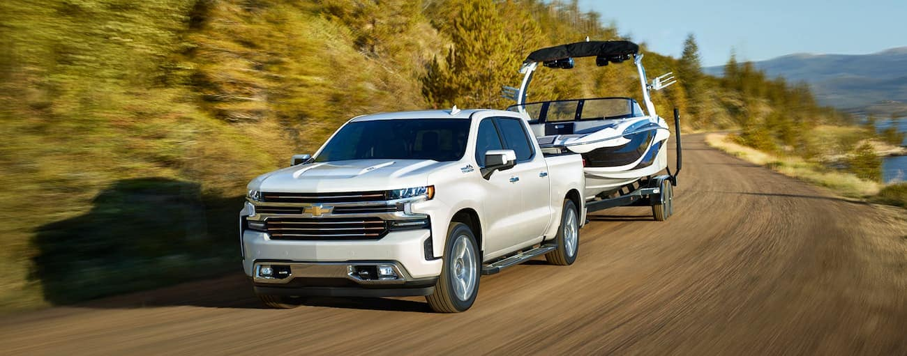 A white 2019 Chevy Silverado towing a boat on a woodland road