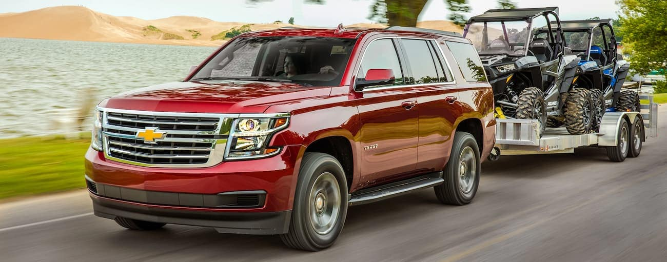 A red 2019 Chevy Tahoe towing a trailer with off road vehicles