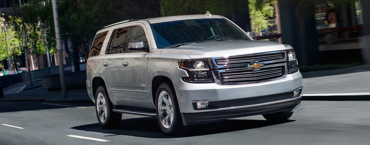 A silver 2019 Chevy Tahoe drives on a city street