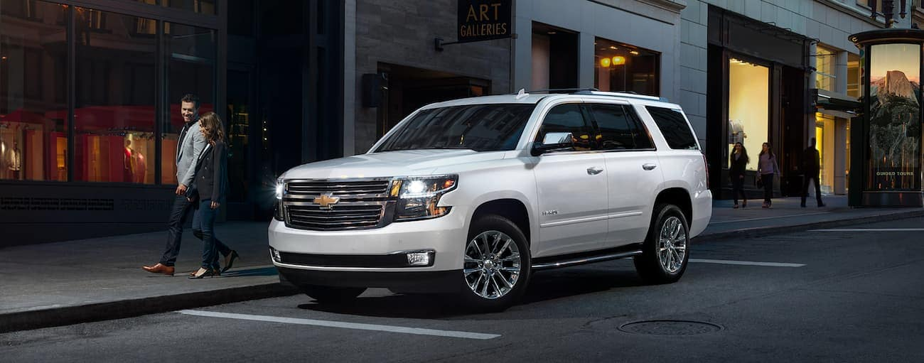 A white 2019 Chevy Tahoe on a city street at night
