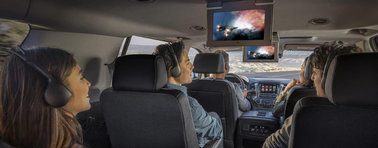 A family watching the onboard screens in a 2019 Chevy Tahoe