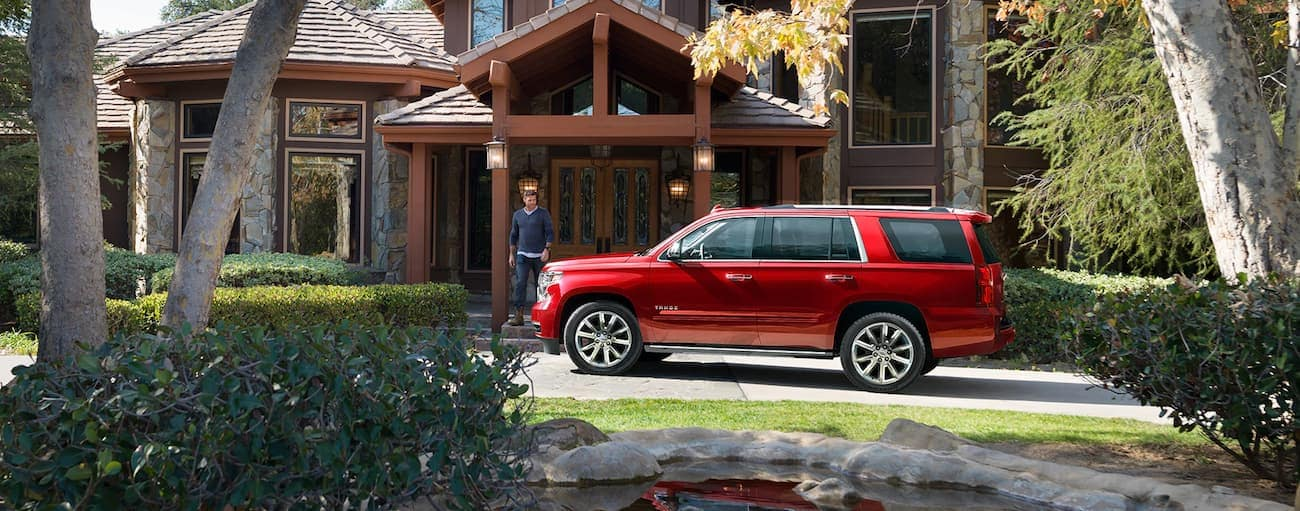 A man leaves a mansion walking towards a red 2019 Chevy Tahoe