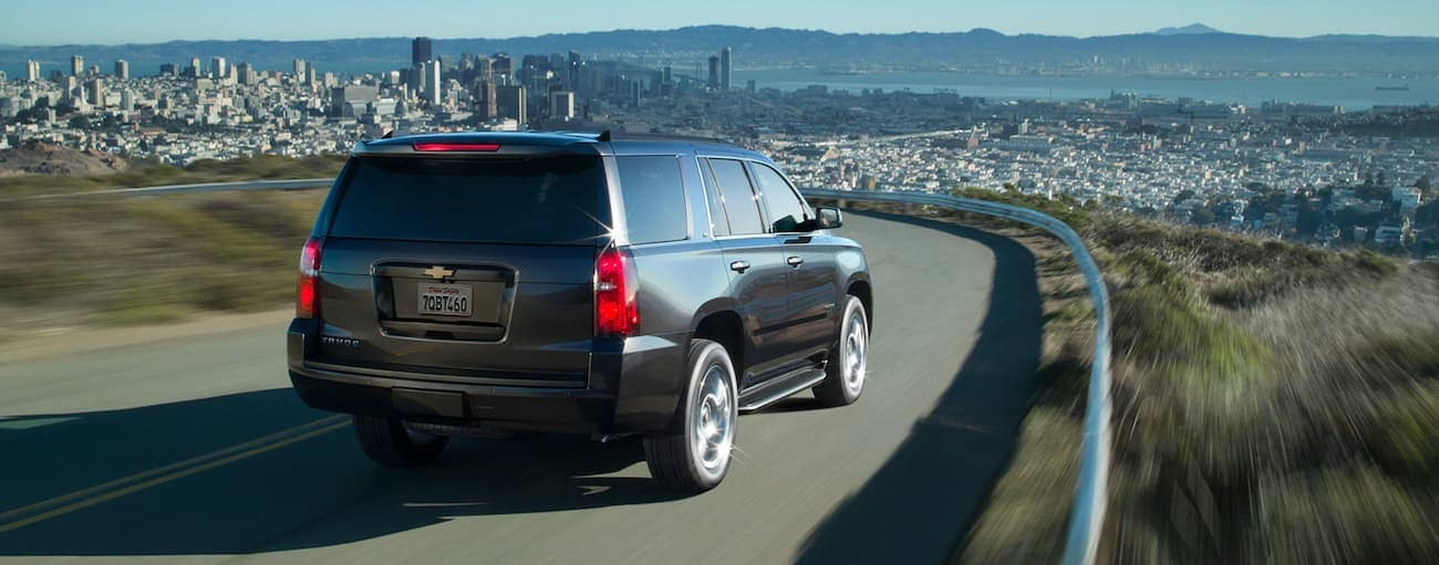 A black 2019 Chevy Tahoe driving around a winding mountain road with a city in the back